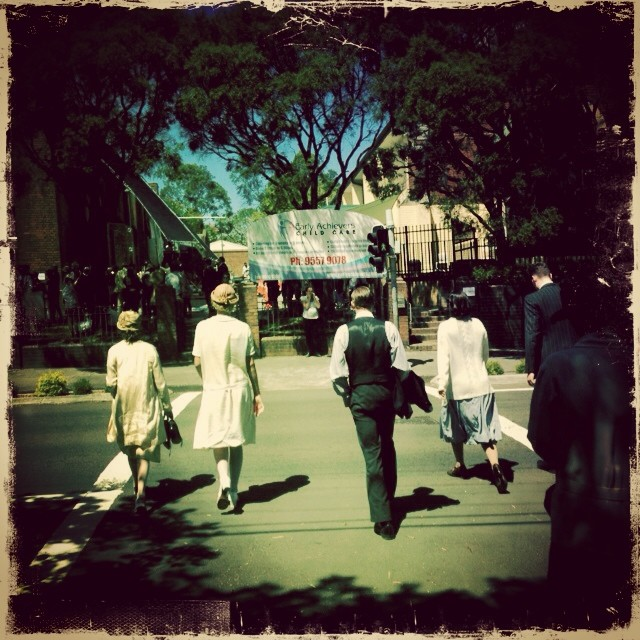 Extras in period costume cross the street for Unbroken